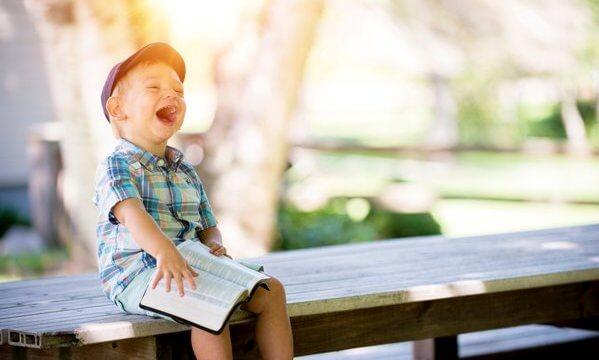 本を持って大笑いする子ども(EC)